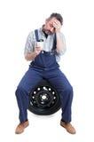Meccanico stanco che si siede sulla gomma e sul caffè bevente immagine stock