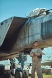 Meccanico in uniforme che sta vicino ad un combattente-intercettore di guerra in un museo all'aperto fotografia stock