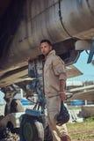 Meccanico in uniforme che sta vicino ad un combattente-intercettore di guerra in un museo all'aperto immagine stock