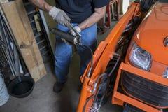 Meccanico Using un ingrassatore a siringa Immagine Stock