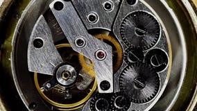 Meccanismo d'annata dell'orologio che lavora macro acciaio filtrato video d archivio