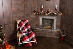 Mecedora con una manta en la sala de estar con m adornado Imágenes de archivo libres de regalías