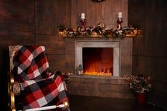 Mecedora en la sala de estar con el fireplac llameante adornado Imagen de archivo