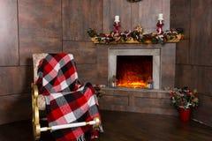 Mecedora en la sala de estar con la chimenea adornada Foto de archivo libre de regalías