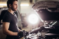 Mechachic checking on car engine and taking notes in clipboard. Concentrated mechanic writing on clipboard in repair garage Royalty Free Stock Image