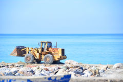 A mechancial digger. A mechanical digger building sea defences Royalty Free Stock Images