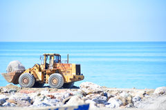 A mechancial digger. A mechanical digger building sea defences Royalty Free Stock Image