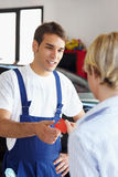 Mechanic. Rear view of woman giving credit card to mechanic royalty free stock image