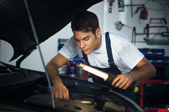 Mechanic. Looking to car engine and holding lamp stock photos