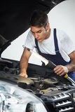 Mechanic. Looking to car engine and holding lamp royalty free stock image