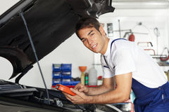 Mechanic. Leaning on bonnet with tester equipment and looking at camera stock photo