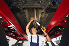 Mechanic. Standing under car engine and holding lamp. Copy space royalty free stock images