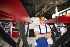 Mechanic. Portrait of mechanic standing under car with arms folded. Copy space stock photography