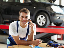 Mechanic. Portrait of mechanic talking on mobile phone in auto repair shop. Looking at camera stock images