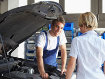 Mechanic. Talking with female client in auto repair shop stock photos