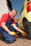 The mechanic. Smiling mechanic is checking the tire pressure royalty free stock photography