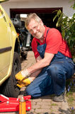 The mechanic. Smiling mechanic is checking the tire pressure stock image