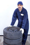 Mechanic. Man with auto wheels royalty free stock photos