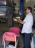 Mechanic 8. Auto mechanic is checking fluid levels on an automobile that is being repaired Royalty Free Stock Photography