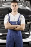 Mechanic. A mechanic with an open hood behind him royalty free stock photography