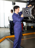 Mechanic Adjusting Alignment Machine On Car. Side view of mechanic adjusting alignment machine on car with colleague working in background at garage Stock Image