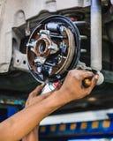 Mechanic adjusting a car drum brake. Hands of a mechanic adjusting a car drum brake Stock Photo