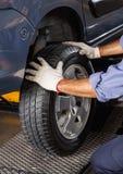 Mechanic Adjusting Car Tire Royalty Free Stock Photo