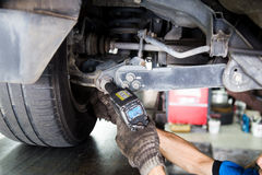 Mechanic adjusting the chamber area during wheel alignment process Stock Photo