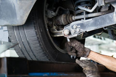Mechanic adjusting the chamber area during wheel alignment process.  Royalty Free Stock Photos