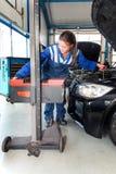 Mechanic, adjusting the hight of a car's head lights Stock Photos