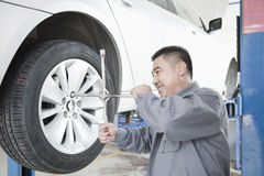 Mechanic Adjusting Tire, Smiling Stock Photo