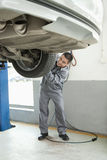 Mechanic Adjusting Tire, Smiling Stock Images