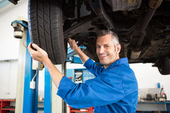 Mechanic adjusting the tire wheel Royalty Free Stock Photos