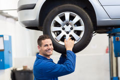 Mechanic adjusting the tire wheel. At the repair garage Royalty Free Stock Photography