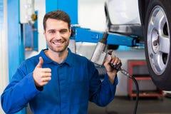 Mechanic adjusting the tire wheel Royalty Free Stock Photo