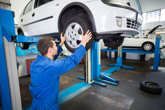 Mechanic adjusting the tire wheel Royalty Free Stock Photo