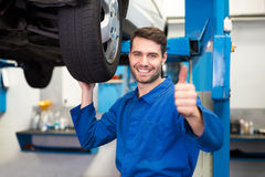 Mechanic adjusting the tire wheel. At the repair garage Royalty Free Stock Image