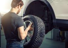 Mechanic adjusting tire wheel at repair garage. Auto Mechanic adjusting tire wheel at repair garage Stock Image