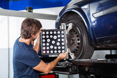 Mechanic Adjusting Wheel Alignment Machine. Male mechanic adjusting wheel alignment machine on car in garage royalty free stock photo