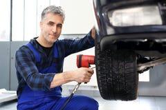 Mechanic adjusts the wheel alignment Stock Image