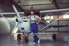 Mechanic and aircraft. Full length portrait of handsome bearded mechanic in uniform looking at camera and smiling while leaning on the aircraft in hangar stock photos