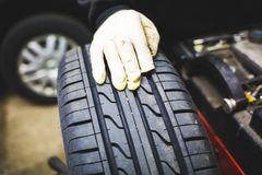 Mechanic aligning car tire at service royalty free stock images