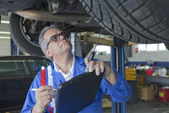 Mechanic analyzing car engine at auto repair shop Royalty Free Stock Photo