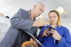 Mechanic and apprentice at repair garage royalty free stock image