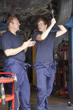 Mechanic and apprentice working on car royalty free stock photography