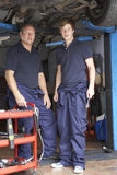 Mechanic and apprentice working on car Stock Photography