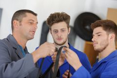 Mechanic and apprentices working on car with computer royalty free stock photo