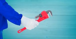 Mechanic arm with wrench against blurry blue wood panel Stock Photos