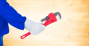 Mechanic arm with wrench against blurry yellow wood panel Stock Photo