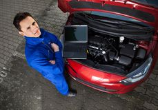 Mechanic with arms crossed standing by car. High angle portrait of confident young mechanic with arms crossed standing by car on street stock photo